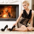 Beautiful blond woman near the fireplace in a luxury interior — Stock Photo