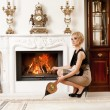 Beautiful blond woman near the fireplace in a luxury interior — Stock Photo #6229034