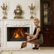 Beautiful blond woman near the fireplace in a luxury interior — Stock Photo #6229037