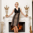 Beautiful blond woman near the fireplace in a luxury interior — Stock Photo #6229038