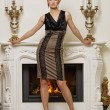 Stock Photo: Beautiful blond woman near the fireplace in a luxury interior