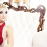 Blond woman sitting on luxury sofa — Stock Photo