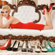 Lady in red dress lying on luxury sofa - Stock Photo