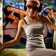 Stylish dancing girl against graffiti background — Stock Photo