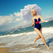 Attractive blond woman running near the sea — Stock Photo