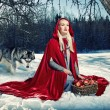 Red hood and a wolf behind her — Stock Photo