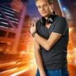Man with headphones against night city background — Stock Photo