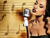 Beautiful singer against abstract background — Stock Photo