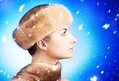 Beautiful young woman in fur cap — Stock Photo