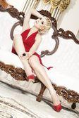 Damen i röd klänning på lyxiga soffa — Stockfoto