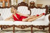 Lady in red dress lying on luxury sofa — Stock Photo