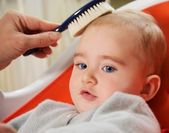 Mother combing her baby's hair — Stock Photo