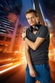 Man with headphones against night city background — Stockfoto