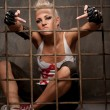 Punk girl behind bars showing rude gesture. — Stock Photo