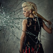 Punk girl with a bat behind broken glass — Stock Photo