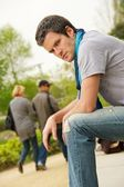 Young man and walking couple on a blurred background — Stock Photo