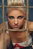 Punk girl behind bars — Stock Photo