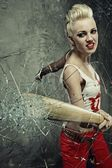 Punk girl broking a glass with a bat — Stock Photo