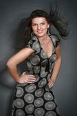 Sexy mladá žena stojící proti šedé pozadí — Stock fotografie
