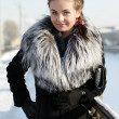 Portrait of the beautiful woman in a fur coat — Stock Photo