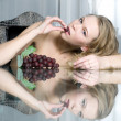 Beautiful blonde is eating grape — Stock Photo