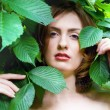Woman's face among the leaves — Stock Photo