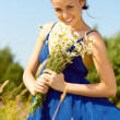 Summer meadow. beautiful woman with bunch of chamomiles — Stock Photo