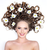 Smiling woman with flowers in hair — Stock Photo