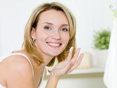 Girl applying moisturizer cream on face — Stock Photo