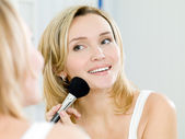 Beautiful young woman doing make-up — Stock Photo