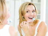 Happy woman cleaning teeth with toothbrush — Stock Photo