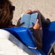 Woman lying on a chaise lounge reading a book on the beach - ストック写真