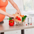 Pregnant woman cooking at kitchen — Stock Photo