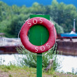 Stock Photo: Red life preserver on green column