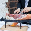 Stock Photo: Waiter while slicing jamon