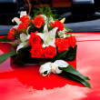Flower's bouquet on a red car — Stock Photo #6660136