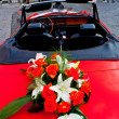 Flower's bouquet on a red car — Stock Photo