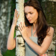 Stock Photo: Sad beautiful girl in a birch grove