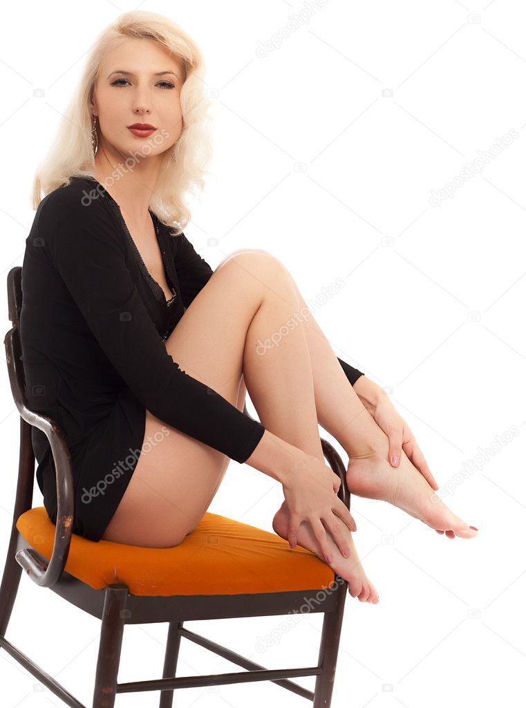 Blonde in a black dress sitting on an ancient chair. isolated on white — Stock Photo #6720906