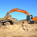 Backhoe loader loading dumper — Stock Photo #5425988