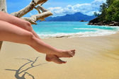 Sand beach, azure sea and woman legs — Stock Photo