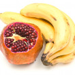 Pomegranate and bunch of bananas — Stock Photo