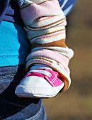 Newborn baby leg in the shoe — Stock Photo