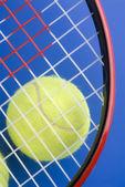 テニス ・ ボールは青い backgro のテニス ラケットの一部の下で — ストック写真