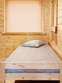 Bed in wooden background — Stock Photo