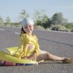 Little Girl sitting on asphalted road — Stock Photo