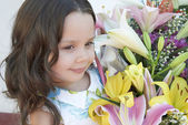 Cute little girl with flowers — Stock Photo