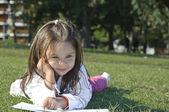 Chica tirado en el césped y leyendo — Foto de Stock