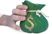 Hand reaching for a money bag — Stock Photo