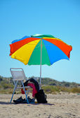 Beach chair and colorful umbrella — Stock Photo